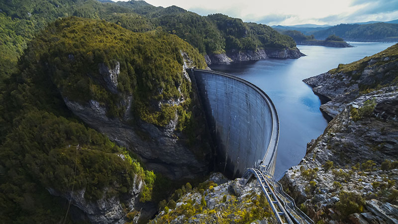 An aerial photo of the Gordon Dam in South West Tasmania, highlighting the stark contrast of the hydroelectric structure and the beauty of surrounding wilderness.